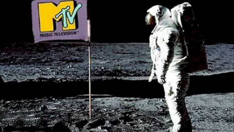 astronaut looking at a banner with an music television emblem on it
